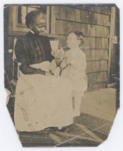 2001.0017.0031, [Photograph of an unidentified woman and an unidentified child on a porch], The Baltimore Collection, University of Delaware Library, Museums, and Press. A white child looks adoringly at a black woman seated on a canvas chair with a cloth over her lap. She holds a teddy bear with articulated arms and legs, presumably trying to entertain the child, but instead the child looks at the woman's face. They are on a porch with a window behind the woman's head and a door just visible on the right edge of the image. There is a geometric flatweave rug beneath the woman and child's feet which extends below and to the left of the visible image.