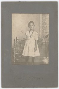 Portrait of a young girl standing wearing a necklace.