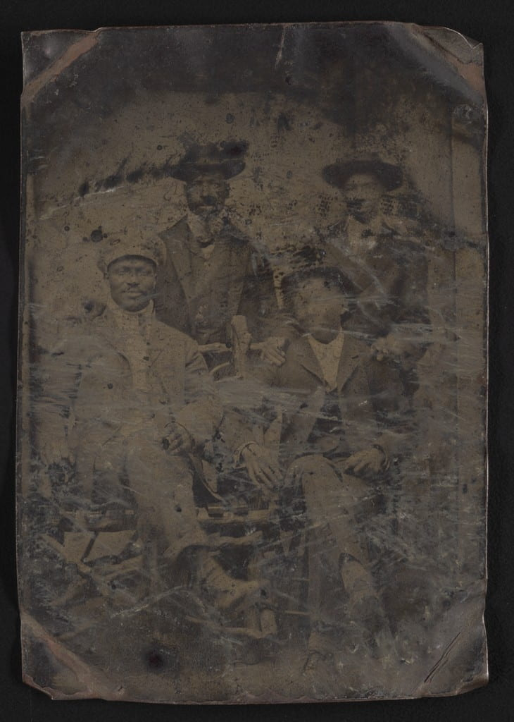 Group portrait of four men, two standing, two seated