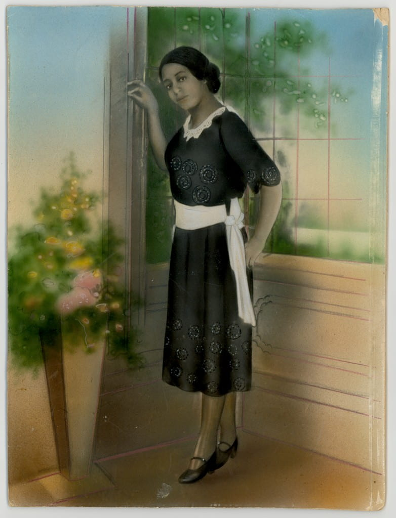 Hand-colored portrait of a woman standing in a domestic interior