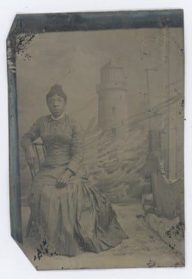 Portrait of an unidentified seated woman in front of a painted backdrop depicting a lighthouse