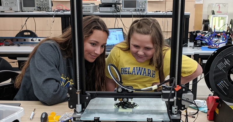 Two students viewing a UD robot