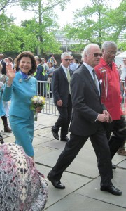 Sweden's Queen Silvia (with flowers) and King Carl XVI Gustaf (in sunglasses) exit the park.