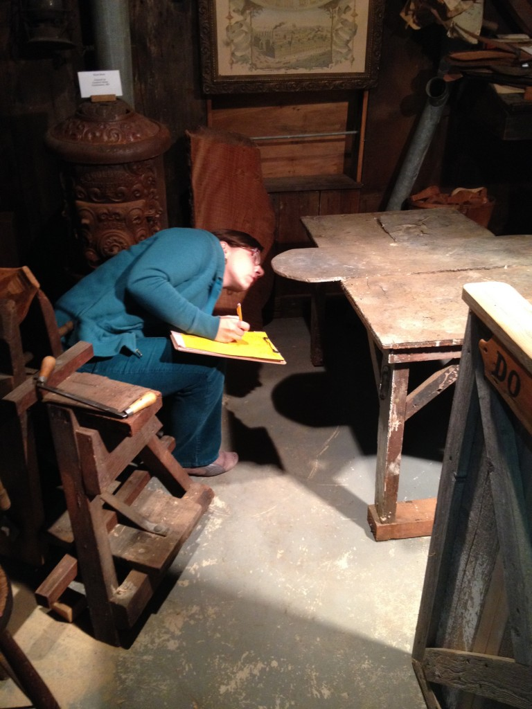 Nicole Belolan cataloguing Paul Gibson's painting worktable inside the Decoy Shop