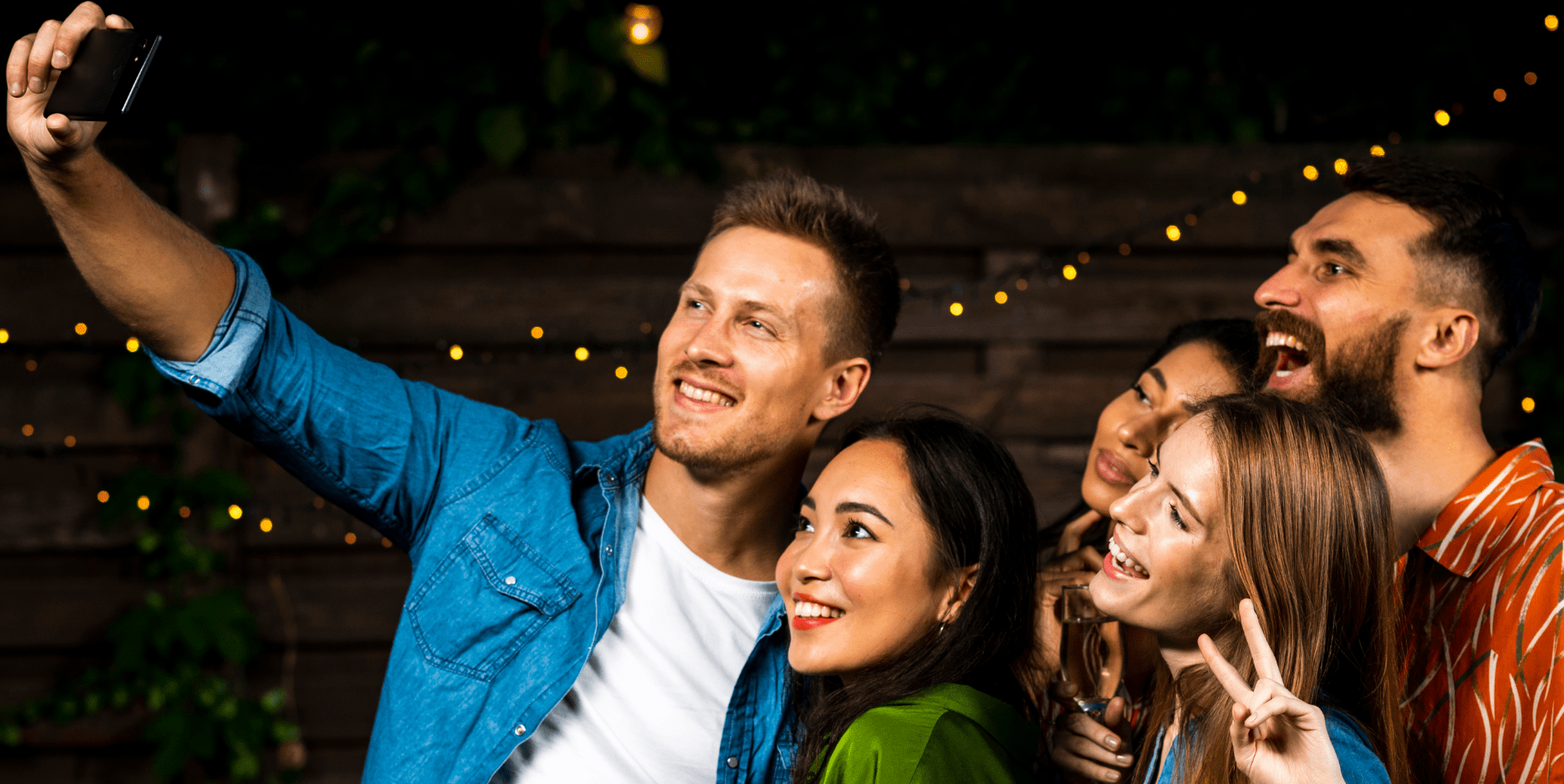 a group of friends smiling together at a backyard party taking a selfie