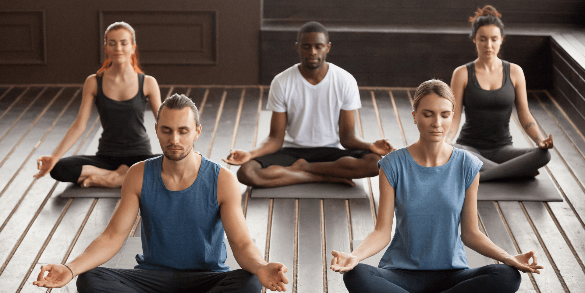 diverse group of people practicing a mediation exercise during a yoga session