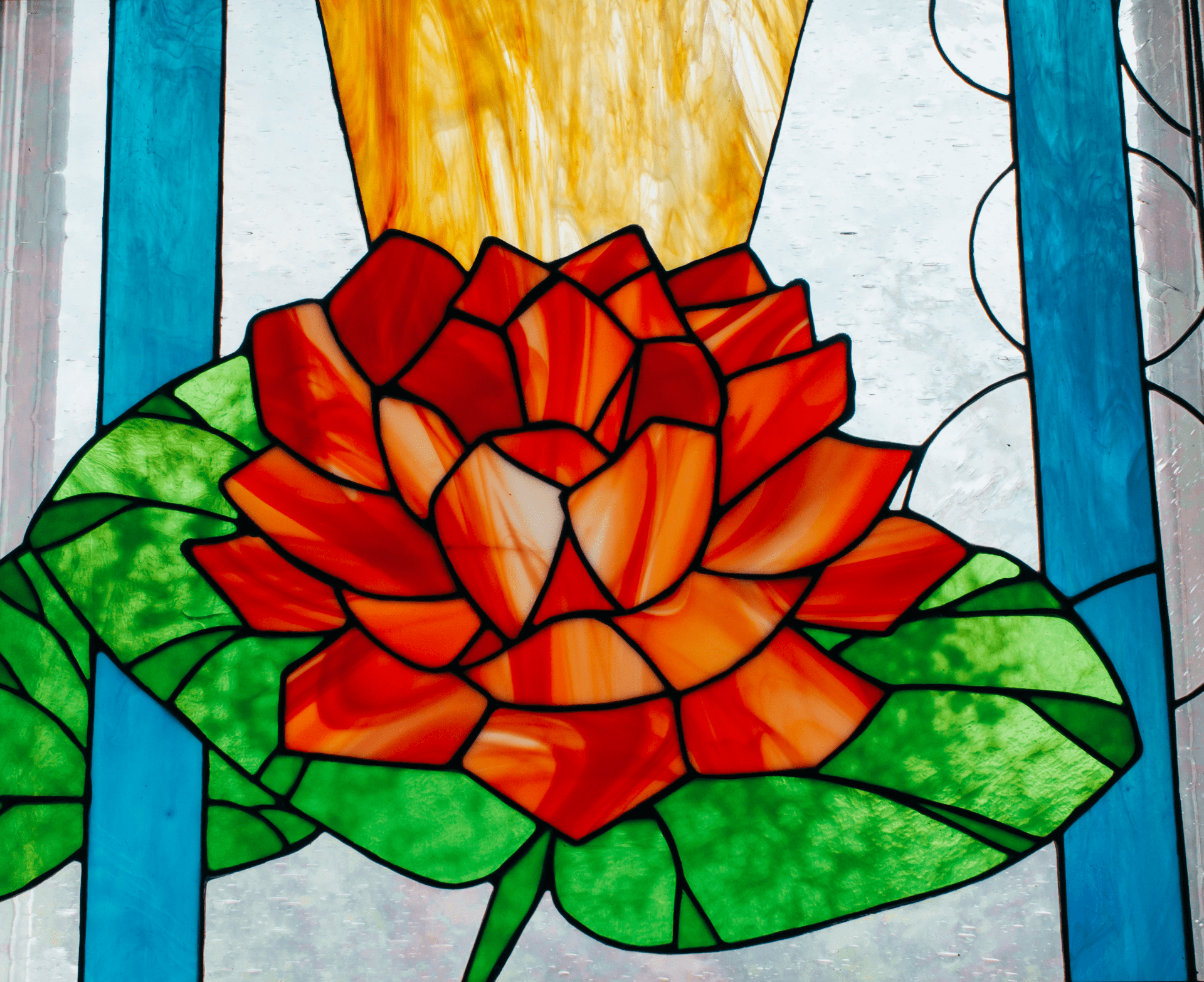 stained glass of a rose on green leaves with gold sun rays in the back and blue stripes along the side.