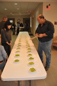 Donald Clifton, a second generation lima bean grower of Milton, DE, examines Baby and Fordhook Lima Beans during the evaluation section of the Lima Bean Forum.