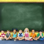 Elementary school students sitting in front of a chalkboard.
