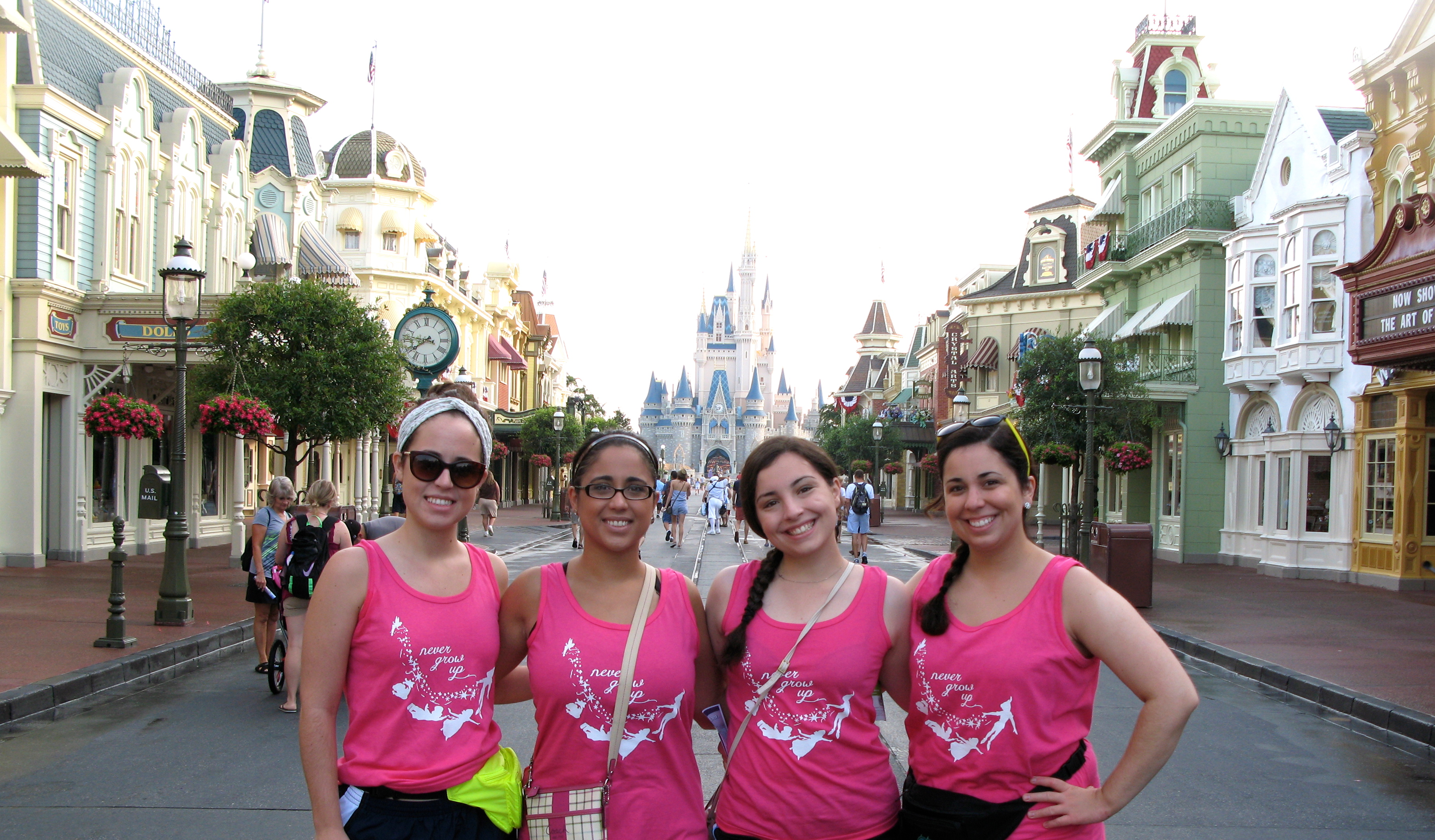 Hannah and her sisters in front of Cinderella's Castle in their matching tanks!