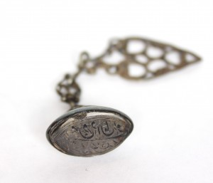 A Persian name written in Arabic calligraphy, dangling from a hand-twisted ornamental chain