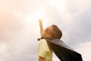 Young boy dressed as superhero with fist to the sky