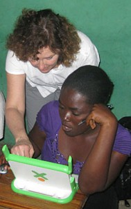 Professor Pollock assists a student with an XO laptop while in Haiti.