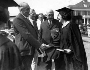 Warren G. Harding, President of the United States, congratulates Mary Haudy, a graduate of the Women''s College of Delaware, during commencement in 1923.