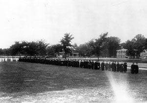 The commencement procession of faculty and graduates at the University of Delaware during the 1920s. They are walking parallel to South College Avenue.