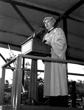 Edward Arthur Trabant, President of the University of Delaware, addresses the graduates at commencement in 1980. Leaning against the railing in front of him is the ceremonial mace carried before the commencement procession. Around his neck, President Trabant is wearing the chain of office. Please click here for more information about the mace and chain of office.