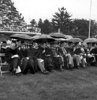 Members of the University of Delaware faculty and professional staff wait out the rain at the 1980 commencement