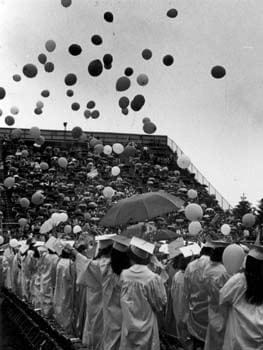Happy University of Delaware graduates release balloons at the 1980 commencement