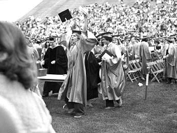 A happy University of Delaware graduate receives his diploma during a commencement ceremony in the late 1970's