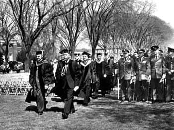 The procession for the University of Delaware commencement of 1965. To the right are pictured ROTC instructors and graduates receiving commissions as officers in the United States Army.