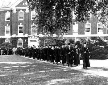 Members of the University of Delaware faculty lead the procession past Evans Hall during commencement in 1965. Following them outside of the left of this photograph would be the graduates, beginning with recipients of doctoral degrees.
