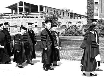 The administration of the University of Delaware proceeds to the commencement ceremonies of 1957. In the background stands P.S. du Pont Hall, which was completed later that year.