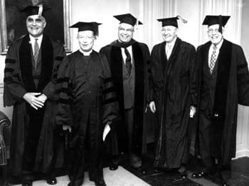 An informal photograph of five honorary degree recipients at the University of Delaware commencement in 1953. Pictured here from left to right are Albert E. Forster (the commencement speaker), Arthur R. McKinstry, John Alanson Perkins (President of the University), Amandus Johnson, and Victor D. Washburn.