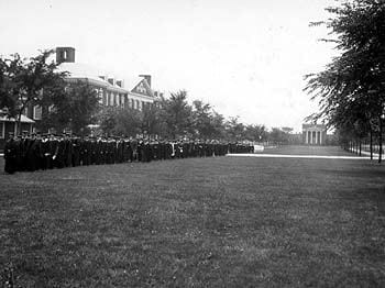 The procession of faculty and graduates during a University of Delaware commencement in the mid-1920s. They are walking on the North Green, with Memorial Hall, Wolf Hall, and an early engineering building in the background. The people wearing white clothing at the rear of the procession are graduates of the Women''s College of Delaware who were receiving two-year degrees rather than the full four-year B.A.
