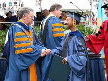 University of Delaware president David Roselle congratulates a graduate of the class of 2003 at commencement.