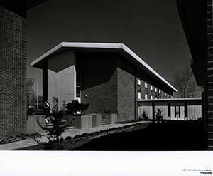 Photograph of Harrington Complex, with a female student walking down the steps. Photo by Lawrence S. Williams, Inc. Photography. 1962.