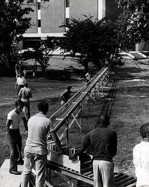 Photograph of a conveyer belt type construction built to facilitate the move from Memorial Hall to Morris Library. Photo by Richard Stewart. 1963.