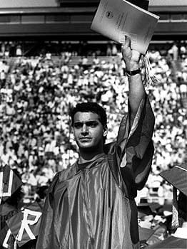 A University of Delaware graduate waves to the audience during commencement in 1990