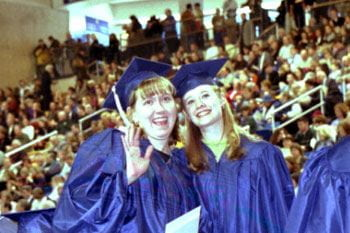 Two graduates of the class of 2001 show their happiness at commencement.