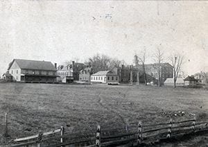 Photograph of the Old College area: View of Old College buildings from the North East, looking over the tract once used as an experimental farm and later landscaped as a portion of Frazer Field. Featured are Men's Gym (no longer in existence), Recitation Hall, Agricultural Experimental Station (now Recitation Hall Annex), Wood Shop (no longer in existence), Old College Hall, green house (no longer in existence), President Raub's House (no longer in existence). Circa 1895-1897.