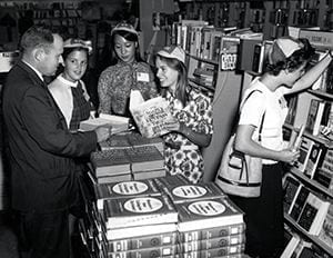 Photograph of a group of female freshmen in the University bookstore, wearing their 1966 beanies. September 11, 1962.