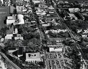 Aerial photograph of Main Street looking east. The image features Willard Hall, McDowell Hall, Old College, Mechanical Hall, Carpenter Sports Building, the George Evans House, and the area where the Trabant Center currently stands. Photo by Eric R. Crossan. Circa 1980.