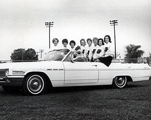 Photograph of cheerleaders and Blue Hen mascot in a car at homecoming. Undated.