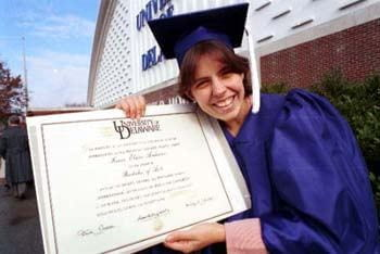 A graduate of the class of 1995 displays her new diploma in front of the Delaware Field House.