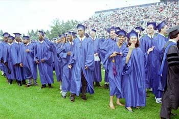 A crowd of happy graduates gathers on the field for the Spring 1993 commencement ceremonies.