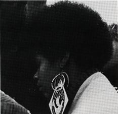 """Student wearing earrings with slogan """"Practice Nonviolence"""" and peace dove from the 1970 yearbook."""