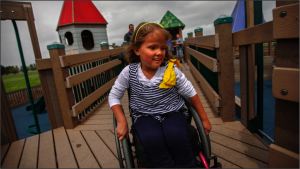Young girl plays in wheelchair.