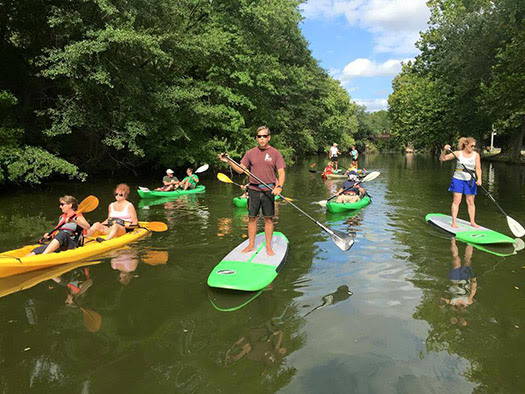Stand up paddle boarders and canoers ride on Broad Creek, part of the Nanticoke Heritage Byway