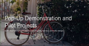 "Image of a bike in a bike rack with the text over top that reads ""Pop-Up Demonstrations and Pilot Projects"""