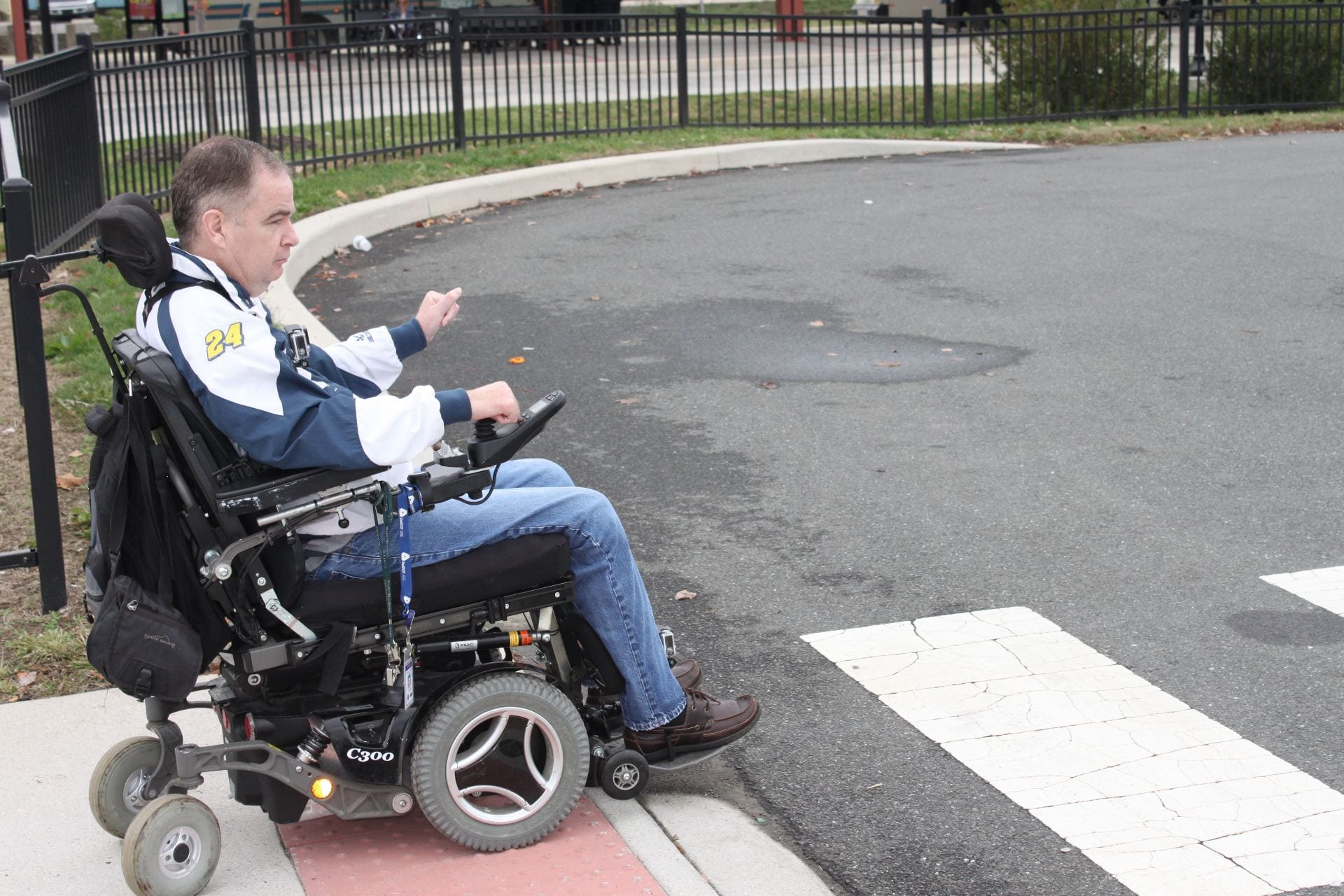 An image of a man using a wheelchair to cross the street, demonstrating the importance of ADA accessibility.
