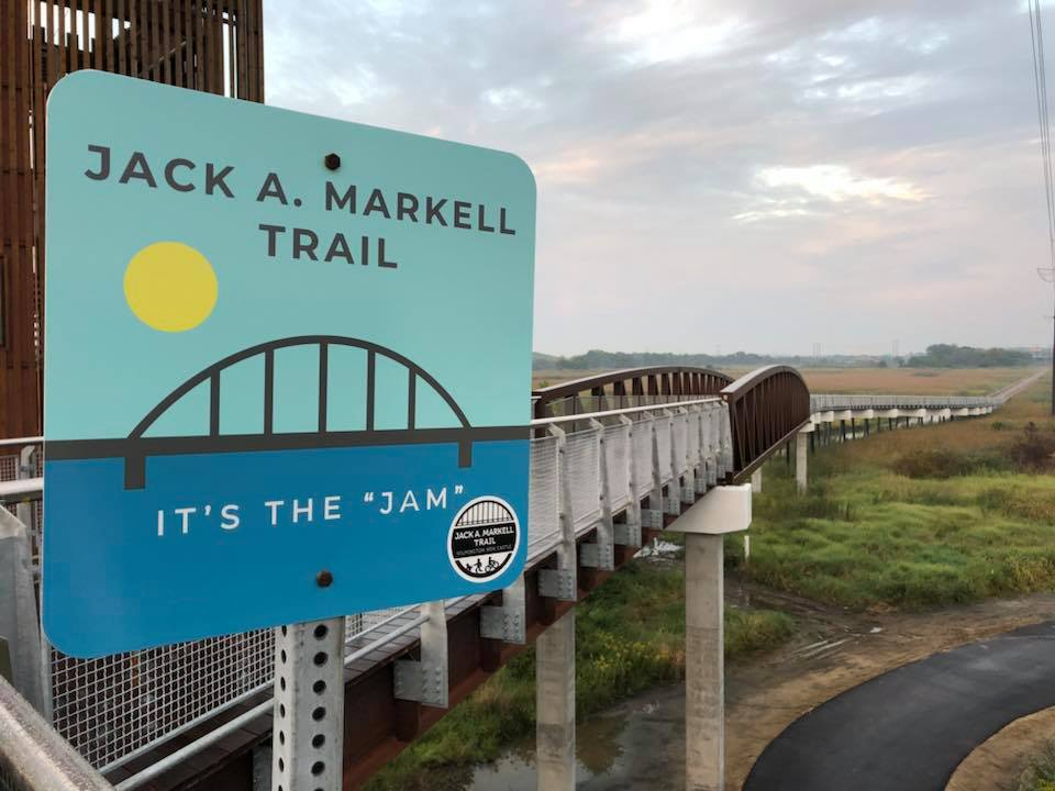 Image of the Jack A. Markell Trail sign and a bridge that forms part of the trail.