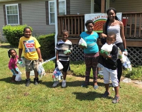 Image of kids showing off their summer grab and go meals from the Summer Nutrition Program at Coverdale Crossroads in Bridgeville.
