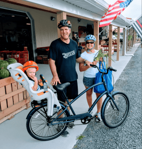 An Image of a family visiting a farmers' market by biking.