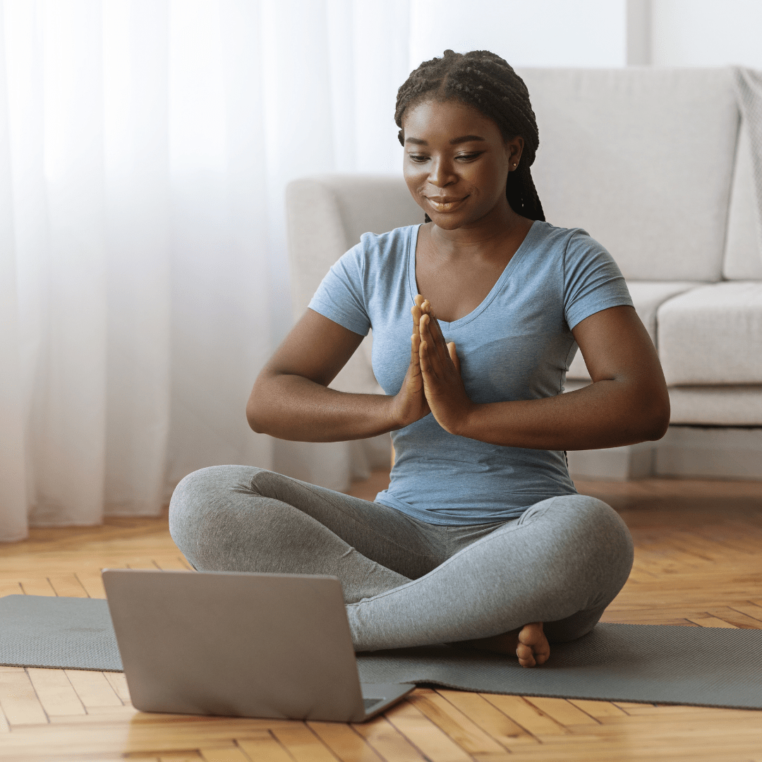 Female doing yoga in front of laptop