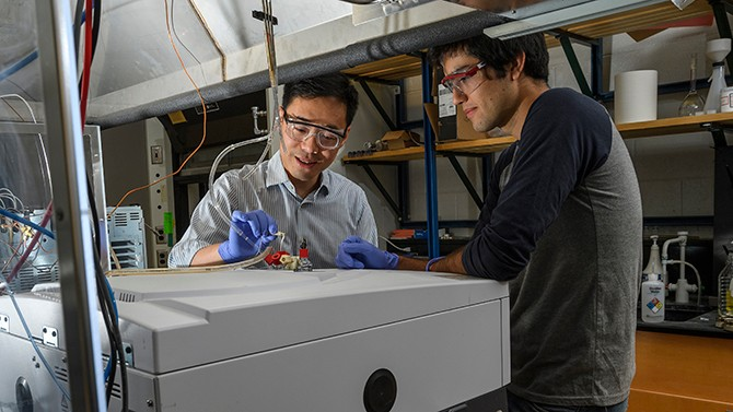 Bingjun Xu (left), shown working in the laboratory with College of Engineering doctoral student Marco Dunwell, has received an Air Force Office of Scientific Research Young Investigator Program grant.