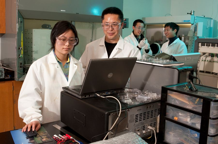 researchers around a laptop